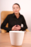 tired woman looking at  cup of coffee poster