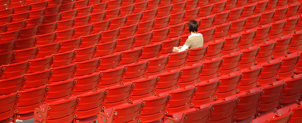 girl alone in the row of red chairs