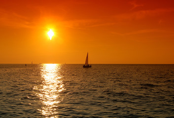 jacht sailing right to the sunset