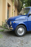 blue italian compact car parked poster