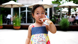 young asian girl having a snack poster