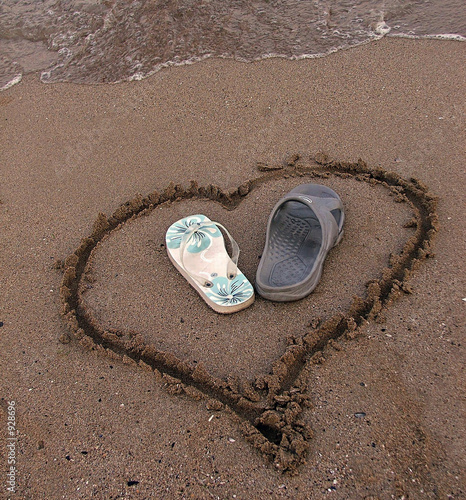 two slipper in a heart on the sand