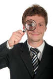 businessman holding magnifying glass poster