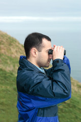 man with binoculars looking at the sea