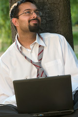 indian with a laptop smiling