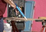 tradesman using a glue gun poster