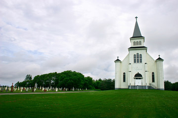 country church and its cemetery under a stormy sky
