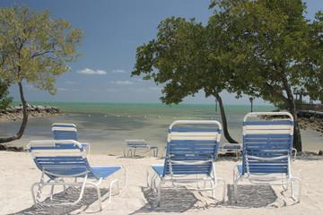 white sand blue chairs