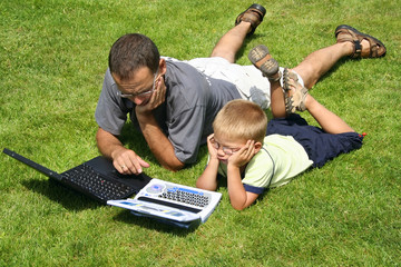boy and his father's working on laptops