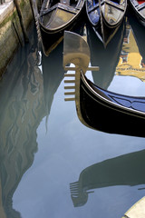 gondolas reflecting on the water, venice, italy.