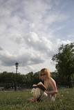 woman sitting in a park and reading a book