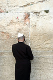 a man praying at the western wall poster