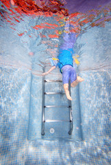 underwater photo of young boy climbing out of swimming pool