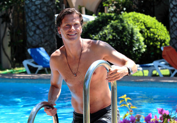 handsome middle aged man climbing out of swimming pool