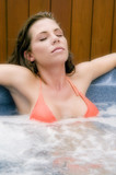 attractive young woamn relaxing in a jacuzzi poster