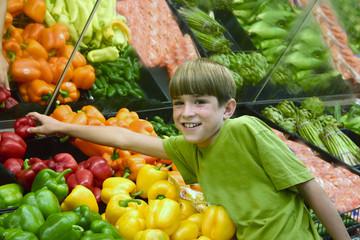 boy reaching for a pepper