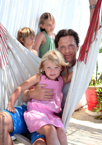 young father and children sitting in a hammock on vacation