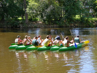 seven canoes with young people in the river