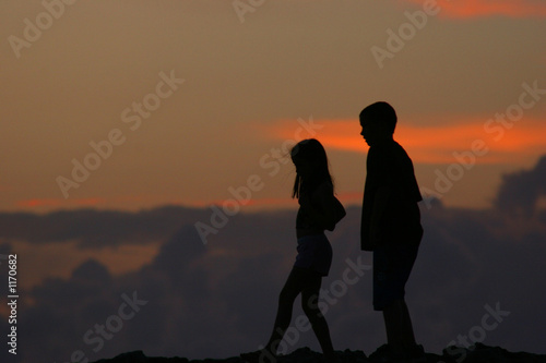 silhouettes of people walking in front of sunset