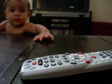 baby reaching for remote control poster