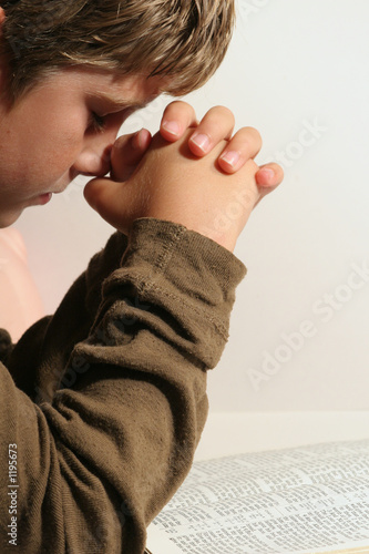 young boy praying vertical