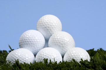 golf ball pyramid on grass against blue sky