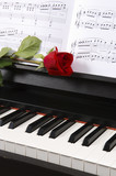 piano with sheet music and a rose poster