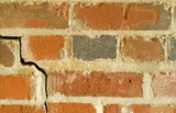 red brick wall with large crack poster