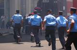 policemen with batons running away