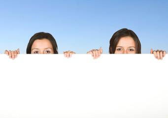 beautiful twins holding a white board