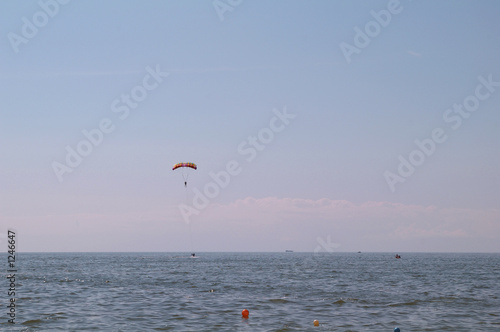 paraglider over a sea on the blue sky.