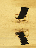 beach chair reflecting in water poster