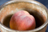 stock photo of a ceramic bowl with peach on blue background poster