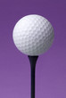 golf ball on blue tee, purple background