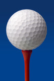 golf ball on red tee, blue background