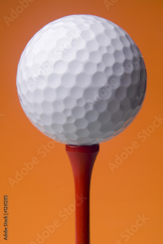 golf ball on red tee, orange background