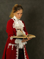 woman in old-fashioned french clothes reading a book
