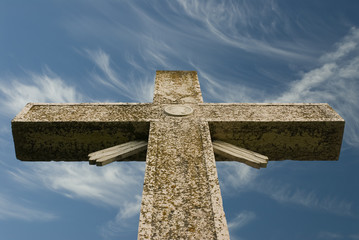 weathered cross with wispy blue sky
