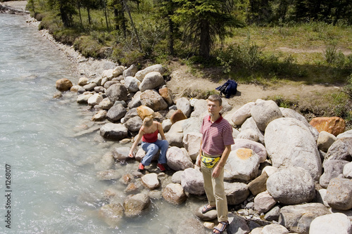 father and daughter at the bank of a river with glacial water