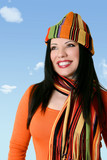 cheerful woman in winter scarf and hat poster
