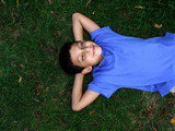 boy laying in grass poster