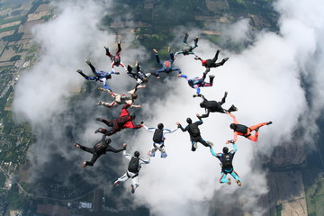 skydivers above clouds