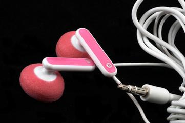 pink earbuds closeup, macro, on black