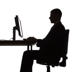silhouette of man working computer