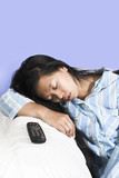 woman sleeping on couch with remote aside