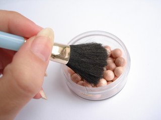 isolated rouge and applicator brush in a hand