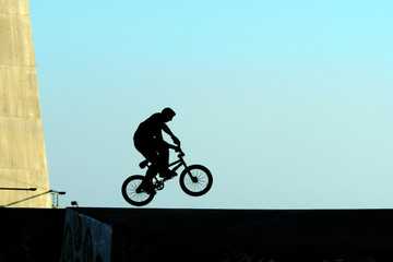 young jumping with bicycle