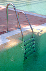 steps leading out of clear green swimming pool