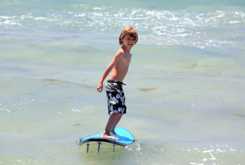 healthy young boy learning to surf