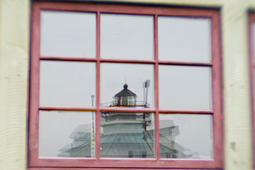 lighthouse reflected in shop window